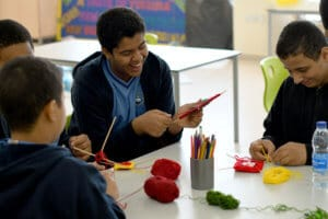 Students with special needs in classroom, working and laughing